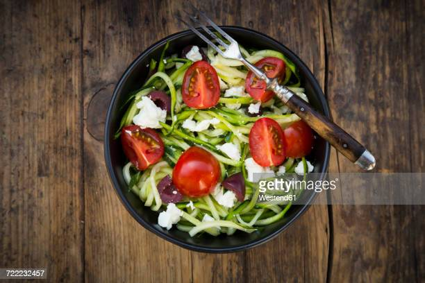 Bowl of zucchini spaghetti with feta, cherry tomatoes and black olives on wood