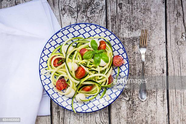 Bowl of zucchini spaghetti with mozzarella, cherry tomatoes and basil on wood