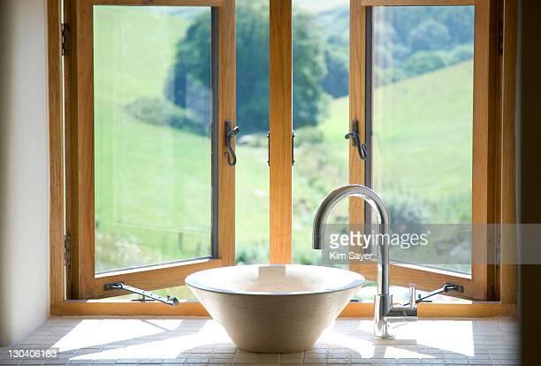 Bowl sink at window in bathroom