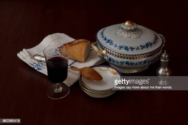Bowl soup, blue and white napkin, glass of wine, silver spoon, bread and salt shaker.
