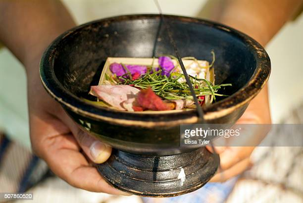 A bowl with an offering of a bamboo basket filled with flowers in Ubud Bali
