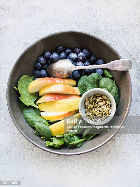 Bowl with blueberries, spinach leaves, sliced pears and pumpkin seeds