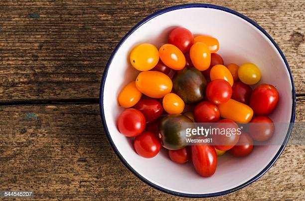 Bowl with different mini tomatoes on wood