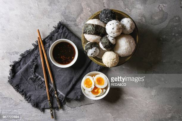 Bowl with different size rice balls with black sesame and seaweed nori, served with soft boiled eggs, soy sauce, chopsticks over gray table. Asian...