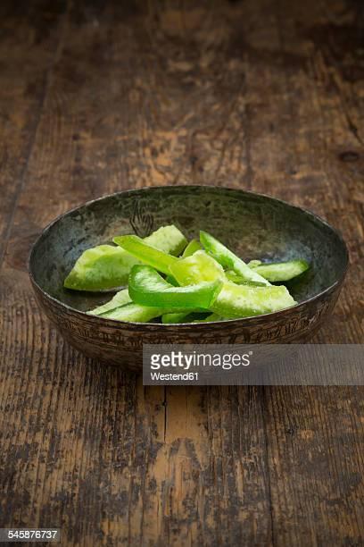 Bowl with dried unripe citron slices, Citrus medica, on dark wood