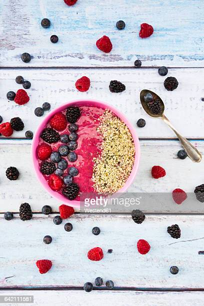 Bowl with fruit smoothie garnished with berries and hemp seeds