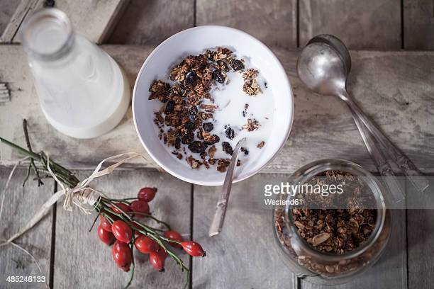 Bowl with granola made of baked oats, nuts and raisins, bottle of milk and rose hips on wooden board