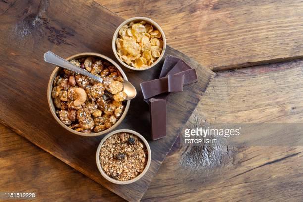 Bowl with granola,corn flakes and dark chocolate bar.