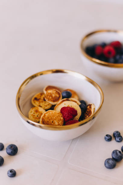 Bowl with healthy mini pancakes and berries