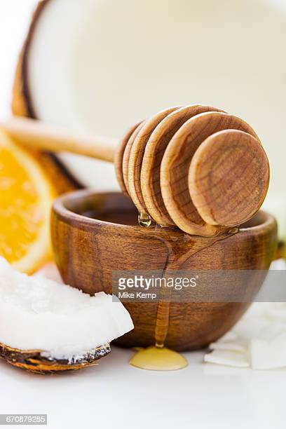 bowl with honey, honey dipper and coconut - bamboo dipper stock photos and pictures