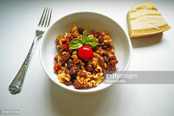 Bowl with Italian pasta meal, on white table, overhead view.