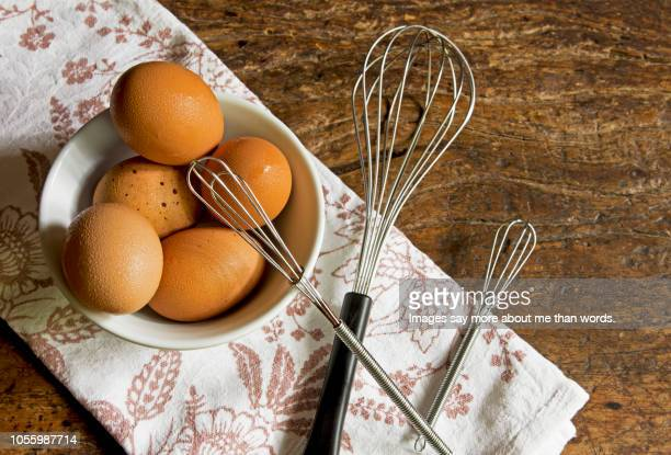 A bowl with many egges over a dish cloth and a wooden table. Still life.