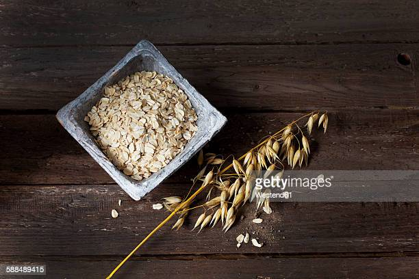 Bowl with oat flakes and ripe spike of oat on wood