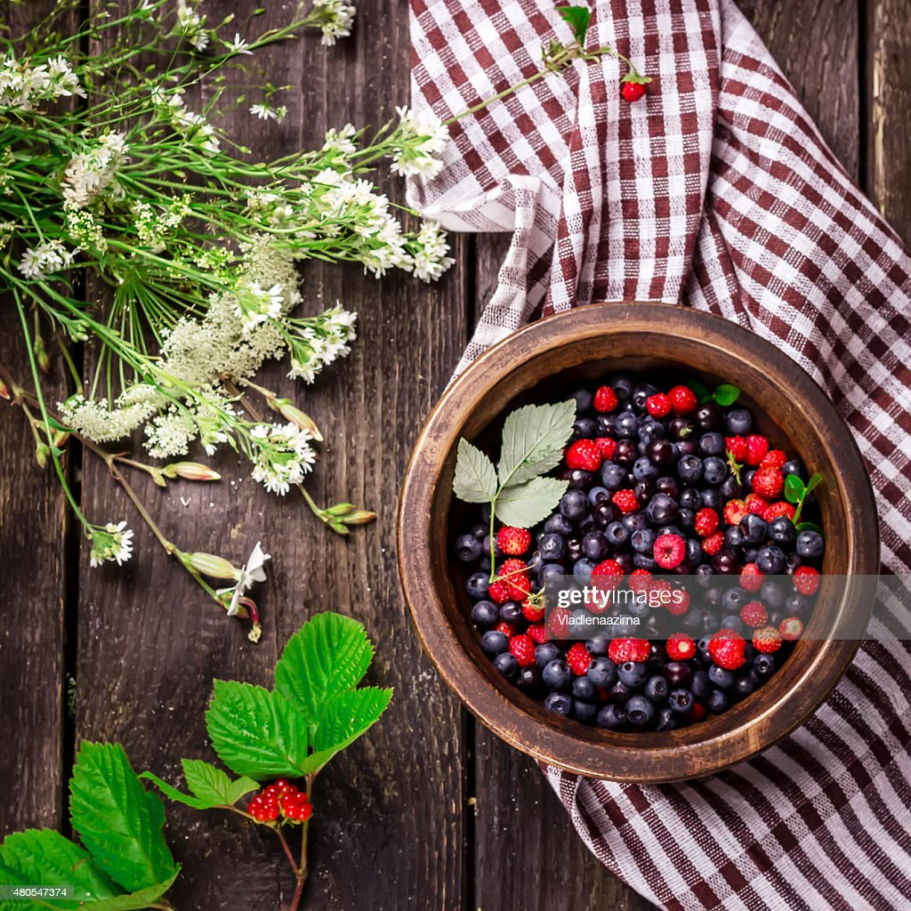 Bowl with wild berries on dark wooden background. : Stock Photo