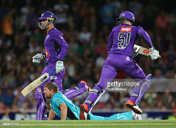 Bowler and captain James Hopes of the Heat falls to the ground as Ben Dunk and Alex Hales of the Hurricanes run between the wickets during the Big...