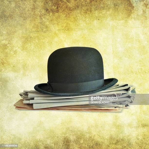 bowler hat on newspapers - hat stock pictures, royalty-free photos & images