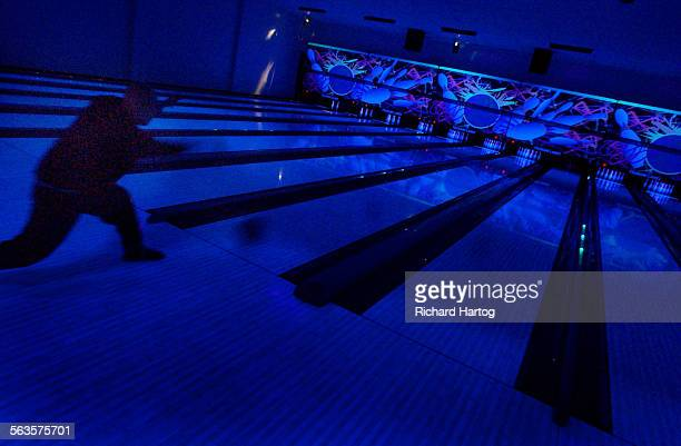 A bowler is silhouetted against the cool black light at the Tsunami Lanes in Cresent City Ca After remodeling the bowling alley is a sparkling beacon...