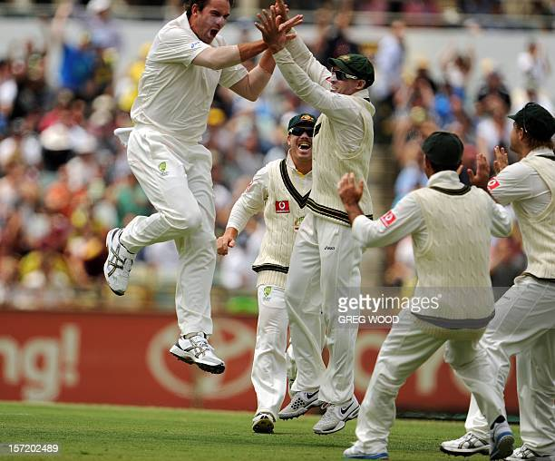 Bowler John Hastings celebrates with teammates after taking the wicket of South African batsman AB Devilliers on day one of the third cricket Test...