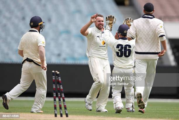 Bowler Jon Holland congratulates wicketkeeper Seb Gotch of Victoria after they dismissed Ashton Turner of Western Australia during day one of the...