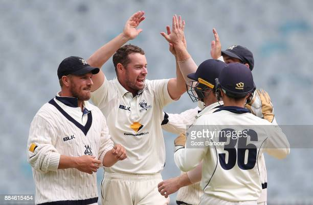 Bowler Jon Holland is congratulated by Aaron Finch of Victoria and his teammates after dismissing Ashton Agar of Western Australia during day one of...