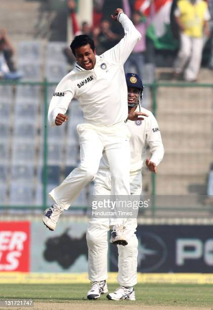 Bowler Pragyan Ojha of India pumps his fist in the air after taking the wicket of West Indies batsman Darren Sammy during the second day of the first...