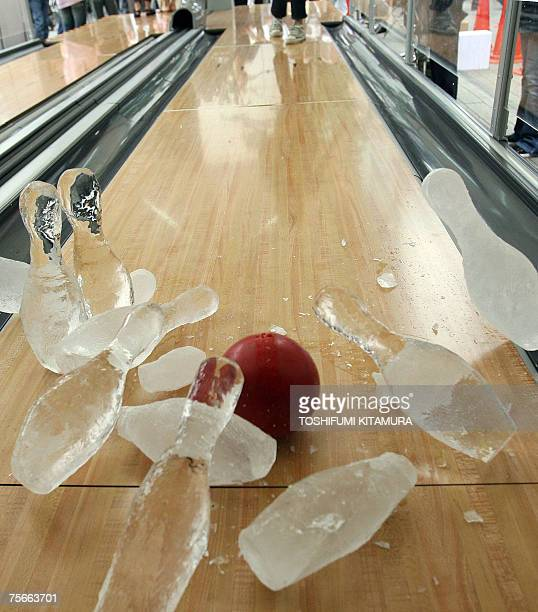 A bowlin ball strikes icemade bowling pins during the opening ceremony of the bowling games in a summer festival in central Tokyo 26 July 2007 A...