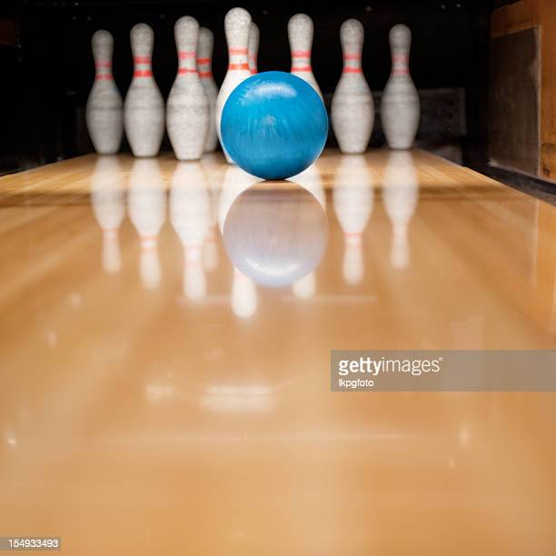 A bowling alley lane with a blue ball and pins