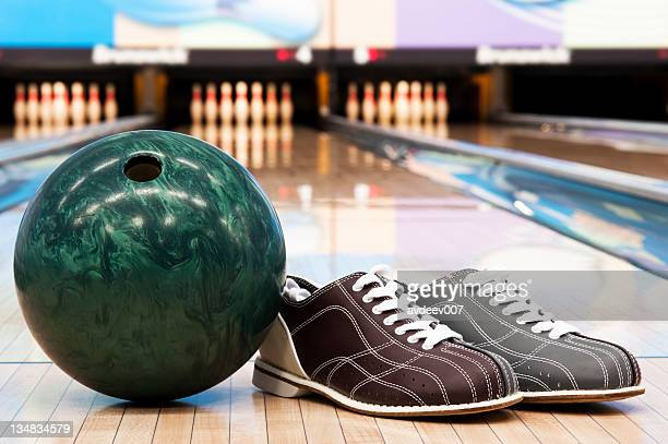 Bowling ball and shoes in bowling alley with background pins