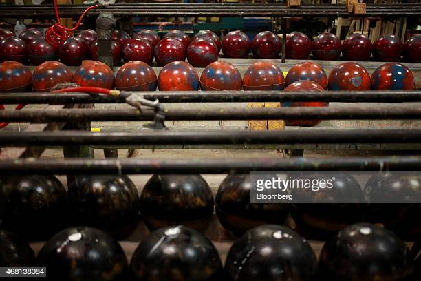 Bowling balls cool on racks after exiting an oven on the assembly line at the Ebonite International manufacturing facility in Hopkinsville Kentucky...