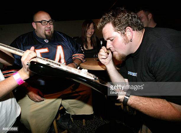 Bowling For Soup guitarist Christopher Van Malmsteen watches drummer Gary Wiseass sniff a permanent marker as he signs a guitar backstage before...