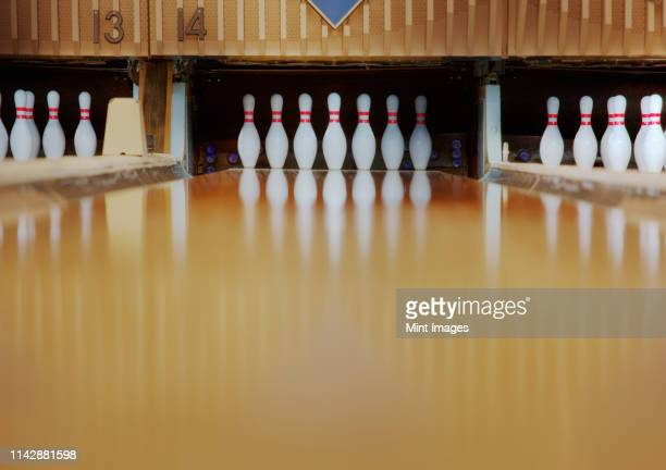 bowling pins reflecting in bowling alley lane - bowling alley stock pictures, royalty-free photos & images