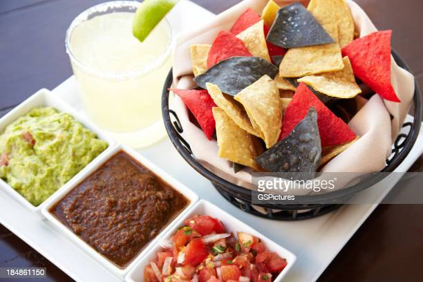 Bowls containing Nachos guacamole and tomato dip with margarita