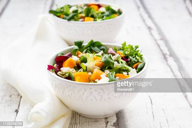 bowls of autumnal salad with feta and hokkaido pumpkin - salad stock pictures, royalty-free photos & images