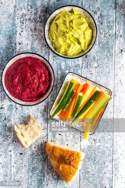 Bowls of beetroot hummus and avocado hummus, crudites and flat bread