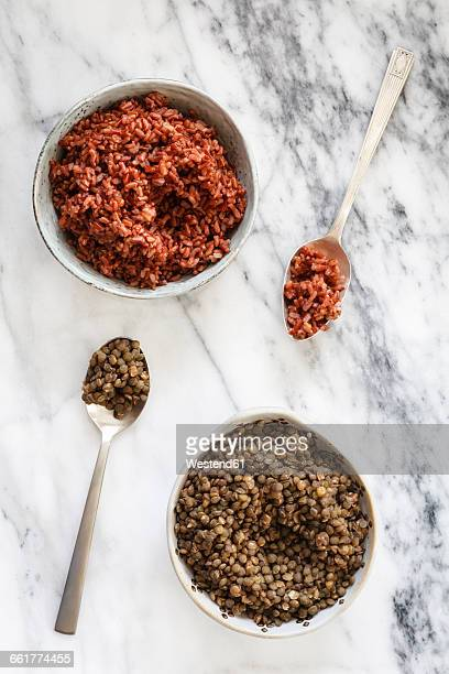 Bowls of boiled red rice andpuy lentils