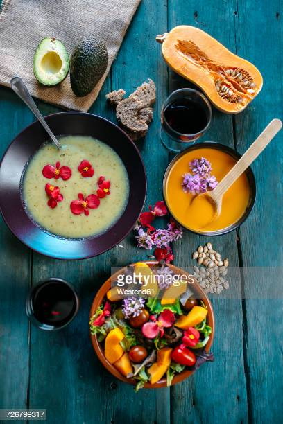 Bowls of creamed pumpkin soup and cream of avocado soup garnished with edible flowers
