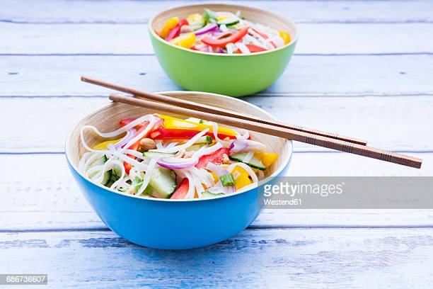 Bowls of glass noodle salad with vegetables on wood