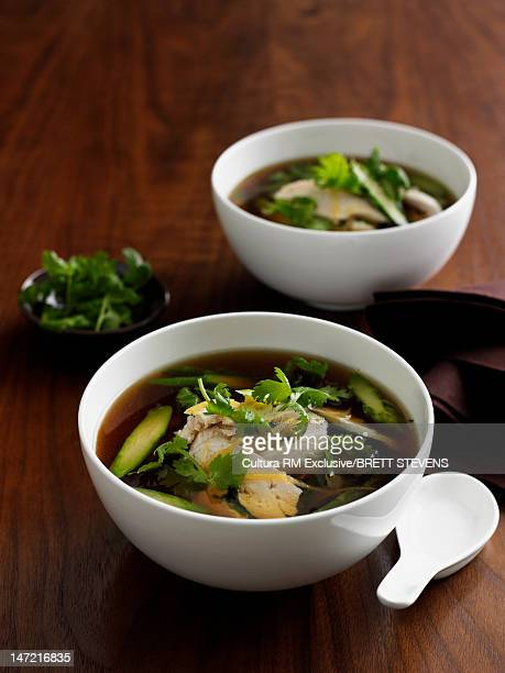 Bowls of meat and vegetables in broth