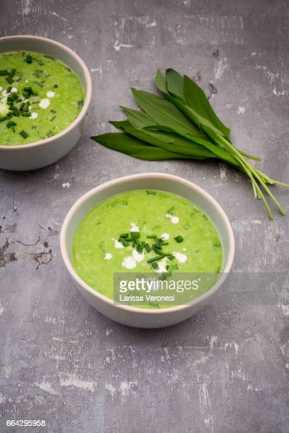 Bowls of organic wild garlic soup and fresh ramson leaves
