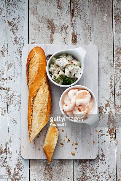 Bowls of pickled herring salad and shrimp salad and baguette on chopping board