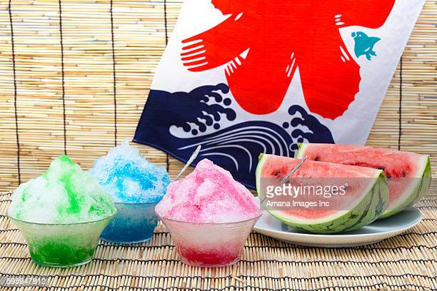 Bowls of shaved ice with syrup, and a watermelon