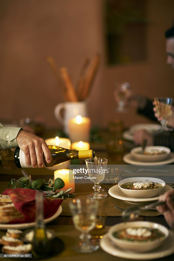 Bowls of soup on dinning table and man pouring wine into glass : Stockfoto