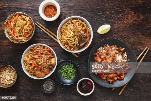 Bowls with chicken, beef and vegetables chow mein and rice with pork