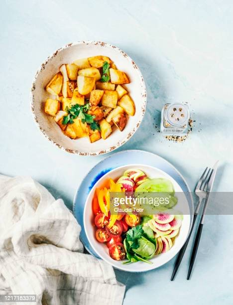 bowls with roasted potatoes and fresh salad on blue background - ローストポテト ストックフォトと画像