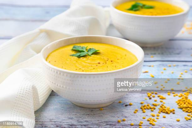 bowls with vegan yellow lentil soup - soup stock pictures, royalty-free photos & images