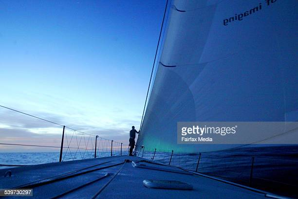 Bowman Morgan White stands on the bow of New Zealand super maxi Konica Minolta as morning light creeps over the horizon in Bass Strait during the...
