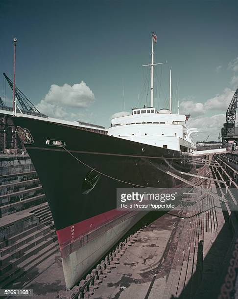 Bows view of the Royal Yacht Britannia undergoing maintenance in a dry dock circa 1955