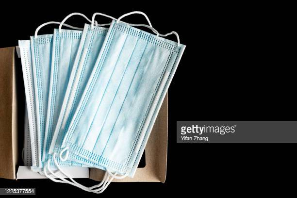 a box of blue medical masks with black background - pollution mask stock pictures, royalty-free photos & images
