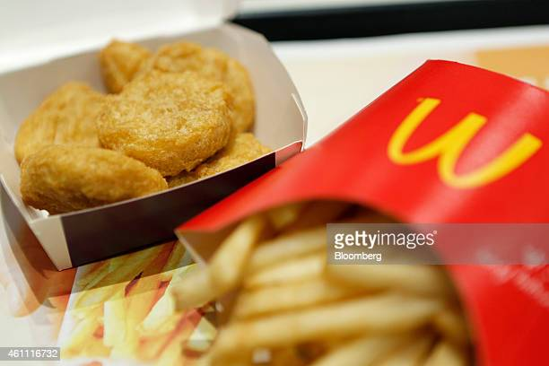 A box of chicken nuggets left sits beside a portion of french fries in this arranged photograph at a McDonald's restaurant operated by McDonald's...