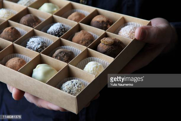 box of chocolates in male hands on a dark background - box of chocolate stock pictures, royalty-free photos & images